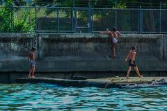 Rzeczny widok ch?opiec bawi? si? przy zatok? Dzieci skacze w wod? obrazy royalty free