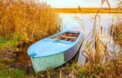 Rzeka i błękitna wioślarska łódź Obrazy Stock