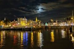 Rzeka iluminującym pejzażem miejskim przeciw niebu przy półmrokiem fotografia stock