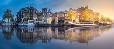 Rzeka, kanały i tradycyjni starzy domy Amsterdam, obraz royalty free