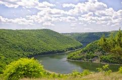 Rzeka między zielonymi wzgórzami z niebieskim niebem Zdjęcie Royalty Free