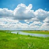Rzeka w zieleni niebieskim niebie i krajobrazie fotografia stock
