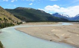 Rzeka z śnieg nakrywać górami w tle Zdjęcia Stock