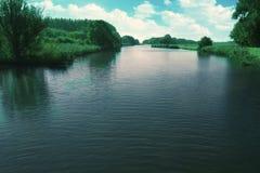 Rzeka z krzakami, łąkami i niebieskim niebem, obraz royalty free