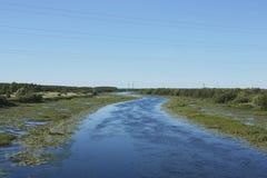 Rzeka z wyginać się wodnymi lelujami i riverbed Zdjęcia Stock