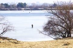 Rzeka zakrywa z lodem Na bankach drzewa, rybaka chwyta ryba Na horyzoncie budynek cityscape zdjęcie royalty free