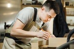 Rzemieślnik odległości między drewnianymi deskami z pomocą władca miara obrazy stock