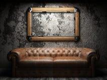 Rzemienna kanapa i rama w ciemnym pokoju Zdjęcia Royalty Free