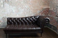 Rzemienna kanapa w Angielskim stylu w pokoju z stary ceglany wal Zdjęcie Royalty Free