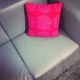 Rzemienna kanapa z czerwieni poduszką Zdjęcie Royalty Free