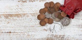 Rzemienna torba rzadkie Stany Zjednoczone monety na białym nieociosanym drewnie obraz stock