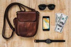 Rzemienna torba, smartphone, okulary przeciwsłoneczni, zegarek, pieniądze na drewnianym tle Mężczyzna ` s akcesoria Strój podróżn zdjęcie royalty free