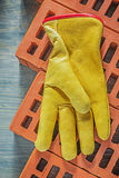Rzemienne ochronnych rękawiczek czerwone cegły na drewnianej deski constructio Obraz Stock