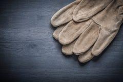Rzemienne pracujące rękawiczki na zmrok desce Fotografia Stock
