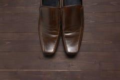 Rzemienni buty są na drewnianym tle Obrazy Royalty Free
