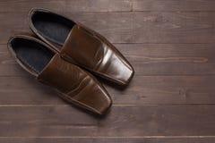 Rzemienni buty są na drewnianym tle Obraz Stock