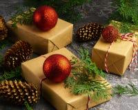 Rzemiosło papier Przedstawia pudełko sznura gałąź Jedlinowych Czerwonych piłek Suchą Pokrojoną Pomarańczową owoc na Betonowym tle obrazy royalty free