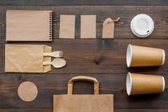 Rzemiosło papierowego koloru set Papierowa torba, rozporządzalny tableware, notatnik na drewnianej tło odgórnego widoku wzoru kop Zdjęcia Royalty Free