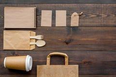Rzemiosło papierowego koloru set Papierowa torba, rozporządzalny tableware, notatnik na drewnianej tło odgórnego widoku wzoru kop Obrazy Stock