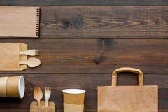 Rzemiosło papierowego koloru set Papierowa torba, rozporządzalny tableware, notatnik na drewnianej tło odgórnego widoku wzoru kop Fotografia Royalty Free
