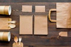 Rzemiosło papierowego koloru set Papierowa torba, rozporządzalny tableware, notatnik na drewnianym tło odgórnego widoku wzorze Fotografia Royalty Free