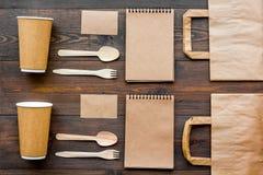 Rzemiosło papierowego koloru set Papierowa torba, rozporządzalny tableware, notatnik na drewnianym tło odgórnego widoku wzorze Obrazy Royalty Free