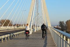 Rzeszow, Polen - 9 9 2018: Een kerel met een meisjes berijdende fietsen op een brug van de opschortingsweg over de Wislok-Rivier  royalty-vrije stock foto