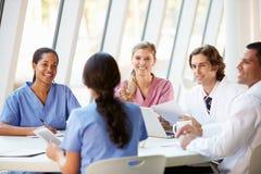 Ärzteteam-Sitzung um Tabelle im modernen Krankenhaus Stockbild