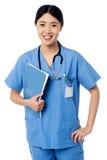 Ärztin, die Patientenaufzeichnungen hält Stockfotos