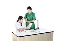 Ärztin mit zwei Asiaten unter Verwendung des Tablet-Computers Lizenzfreie Stockfotos