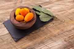 Rzuca kulą pełno świeżej owoc kumquat na drewnianym tle Fotografia Stock