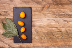 Rzuca kulą pełno świeżej owoc kumquat na drewnianym tle Obraz Stock