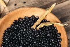 Rzuca kulą z czarnymi haricot fasolami na drewnianym stole, obraz royalty free