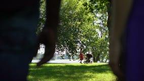 Rzucająca wyzwanie para ogląda szczęśliwej mamy z dziecko frachtem w parku zdjęcie wideo