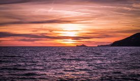 Sunset in Marina di Carrara. Beautiful blazing sunset in mediterranean sea landscape and orange sky above it with awesome sun golden reflection on calm stock images