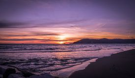 Sunset in Marina di Carrara. Beautiful blazing sunset in mediterranean sea landscape and orange sky above it with awesome sun golden reflection on calm stock photos