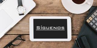 SÃguenos, Follow的西班牙文本我们在片剂comput屏幕上  免版税库存图片