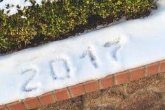 2017 são escritos na neve branca A neve encontra-se no parapeito Foto de Stock