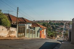 Downhill street view with sidewalk walls and colorful houses on a sunny day at São Manuel. Stock Images