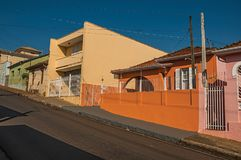 Working-class colored houses and fences in an empty street on a sunny day at San Manuel. São Manuel, southeast Brazil - October 14, 2017. Working-class stock photography