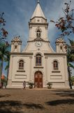 Pedestrian walking in front The Matriz Church and green garden in a sunny day at São Manuel. royalty free stock images