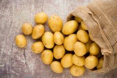 Säck av nya rå potatisar på träbakgrund, bästa sikt arkivfoton