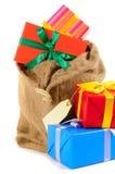 Säck- eller strumpapåsen fyllde med julgåvor som isolerades på vit bakgrund Royaltyfria Foton