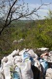 Säckar som fylls med avskräde mot naturen Arkivfoton