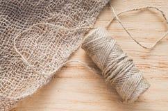 Säckväv- och skeinjute tvinnar på en träbakgrund, den selektiva fokusen, lantlig stil Arkivfoto