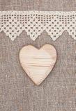 Säckvävbakgrund med den spets- torkduken och trähjärta Arkivbilder