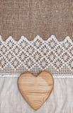 Säckvävbakgrund med den spets- torkduken och trähjärta Arkivfoto