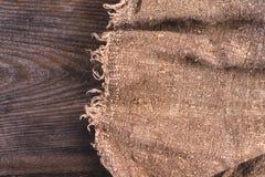 Säckvävhessians som plundrar på träbakgrund Arkivbild