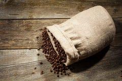 Säckvävsäck av kaffebönor mot mörk wood bakgrund Royaltyfri Bild