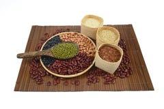 Sädes- korn och fröbönor som är användbara för hälsa i wood skedar på vit bakgrund Arkivbilder